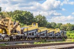 Afleidende die locomotief met wagens met complexen voor de bouw en de reparatie van spoorwegsporen worden uitgerust stock afbeelding