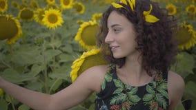 Aforable kobiety kędzierzawy odprowadzenie na słonecznikowym polu Jaskrawy ? zbiory wideo