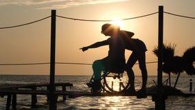 Afortunado lisiado en la silla de ruedas con la mujer que considera en horizonte en fondo del ocaso hermoso el viaje del verano almacen de metraje de vídeo