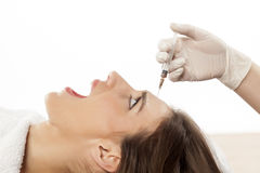 Afraid of botox. Frightened young woman is afraid of injecting botox in her forehead Stock Photography