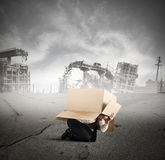 Afraid businessman during crisis. Afraid businessman is hiding under a cardboard in a city destroyed Royalty Free Stock Photography