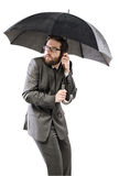 Afraid businessman hiding himself under the umbrella Stock Photo