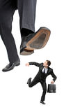 Afraid businessman running away from a big foot Stock Photos