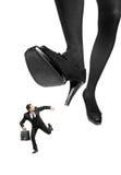 Afraid businessman running away from a big foot Stock Photography