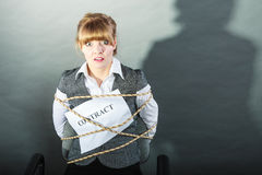 Afraid businesswoman bound by contract terms. Afraid businesswoman bound by contract terms and conditions. Terrified scared woman tied to chair become slave Stock Photos