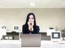 Afraid businesswoman with laptop at office. Businesswoman is biting her nails because shes afraid while sitting in front of laptop at the office Stock Images