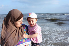 Afraid crying arab muslim baby girl with her mother. Photo of afraid crying arabian baby girl with her mother in local beach in egypt Royalty Free Stock Photography