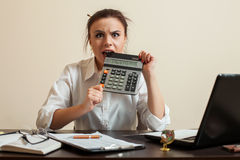 Afraid female bookkeper gnaws calculator Royalty Free Stock Photo