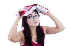 Afraid female student cover head with book - isolated. Beautiful female student cover her head with book, afraid of something falling, isolated on white Stock Image