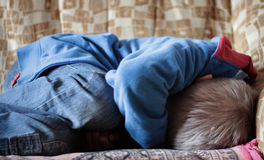 Afraid. Frightened boy in jeans curled up on bed Royalty Free Stock Photos