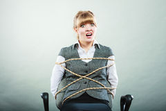 Afraid kidnapped woman tied with rope to chair. Royalty Free Stock Images