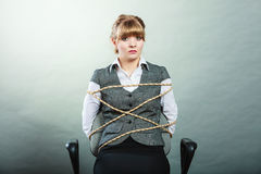 Afraid kidnapped woman tied with rope to chair. Royalty Free Stock Photo