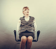 Afraid kidnapped woman tied with rope to chair. Stock Photo