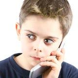 Afraid little boy speaking on the phone in white background. Afraid little boy speaking on the phone on white background Royalty Free Stock Image