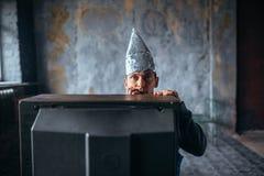 Afraid man in aluminum foil cap watch TV, UFO Royalty Free Stock Images