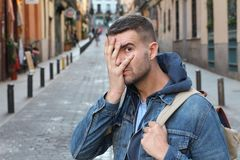 Afraid man hiding his face outdoors.  stock image
