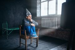 Afraid man in tinfoil helmet watches TV. Paranoia concept. UFO, conspiracy theory, brain theft protection, phobia Stock Photo