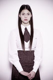 Afraid school girl. Teen school girl wearing formal clothes and standing against a white wall - colorized photo Stock Photos