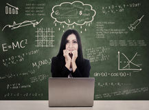 Afraid student facing online test with laptop. Afraid student facing online test while studying with her laptop at school Royalty Free Stock Image