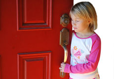 Afraid to leave the house. Young girl waits by the door for her parent to come home, or she is afraid to leave the house because of peer pressure stock photo