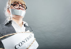 Afraid woman bound by contract with taped mouth. Stock Images