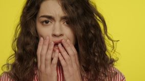 Afraid woman face with open mouth touching face with hands on yellow background. Portrait of scared woman face in studio. Close Up of shocked woman face stock video footage