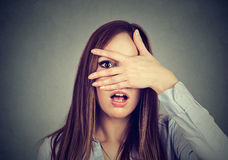 Afraid woman peeking through her fingers Stock Photography