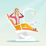 Afraid woman sitting in the dental chair. Frightened patient in the dentist office. Scared caucasain woman visiting a dentist in the dental clinic. Afraid woman Royalty Free Stock Photo
