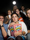 Afraid young woman. Afraid young women at the movie theater with bag of popcorn Royalty Free Stock Images