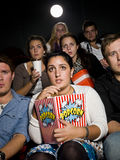 Afraid young woman. Afraid young women at the movie theater with bag of popcorn Stock Photo