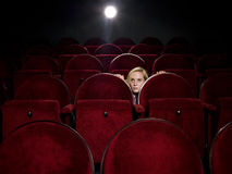Afraid young woman. Alone in the movie theater Stock Images