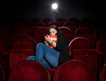 Afraid young woman. Alone in the movie theater Stock Image