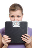 Afraid young woman looking behind a weight scale. Over white background Stock Image