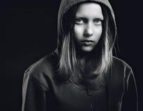 Afraided teen girl in hood. Studio shot Stock Photo