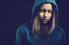 Afraided teen girl in hood. Studio shot Royalty Free Stock Photography