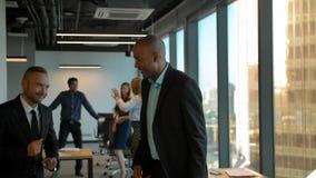 Aframerican y empresarios cauc?sicos que bailan en la oficina coworking metrajes