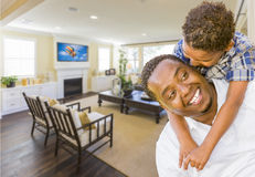 Afrian American Father and Mixed Race Son in Living Room Royalty Free Stock Photography