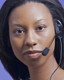 Afrian American woman talking on headset. Portrait of an African American woman talking on a headset Royalty Free Stock Photos