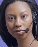 Afrian amerikanische Frau, die auf Kopfhörer spricht Lizenzfreie Stockfotos