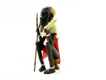 Black African art statuette. Statuette representing an isolated seated black African farmer wearing red clothes Stock Photo