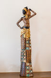Africa figurine girl on table. Africa figurine girl standing on a wooden table on a background of a white wall stock image