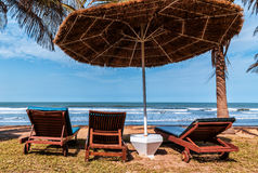 Africa Gambia - paradise beach. Deck chairs under an umbrella of palm leaves on a paradise beach Stock Images