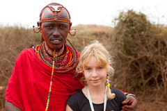 AFRICA, KENYA, MASAI MARA - JULY 2: Male tribal member wearing t. Raditional attire posing for a portrait with European white girl on July 2,2011, in Kenya Royalty Free Stock Photography