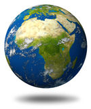Africa on Planet earth. Earth model planet featuring Africa and middle eastern countries surrounded by blue ocean and clouds isolated on white Royalty Free Stock Image