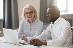 Africain heureux et collègues caucasiens parlant dans le bureau à l'ordinateur portable photo stock