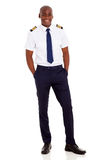 African airline pilot. Cheerful young african airline pilot standing over white background Stock Photography