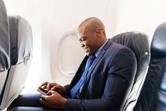 African airplane passenger. Happy african airplane passenger using smart phone on plane Royalty Free Stock Image