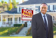 African American Agent In Front of House and Sold Sign royalty free stock image