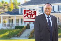 African American Agent In Front of Home For Sale Sign stock image