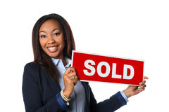 African American Agent Holding Sign. Portrait of African American woman holding sold sign isolated over white background Royalty Free Stock Images